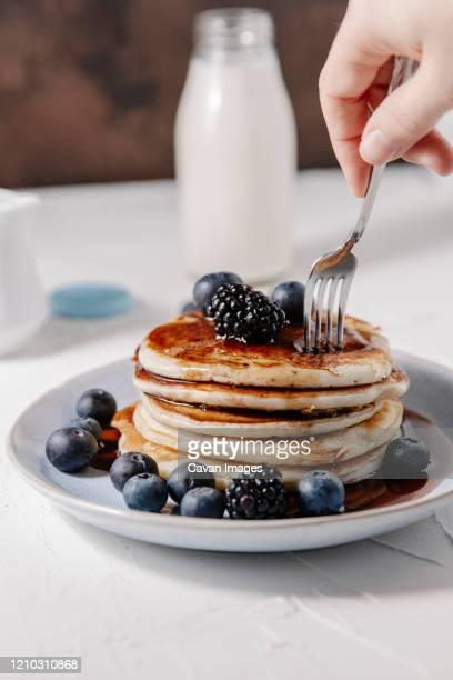 woman sticking a fork into a stack of homemade pancakes with berries - pancakes stock pictures, royalty-free photos & images