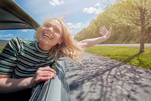 Woman sticking head out of window while driving - gettyimageskorea