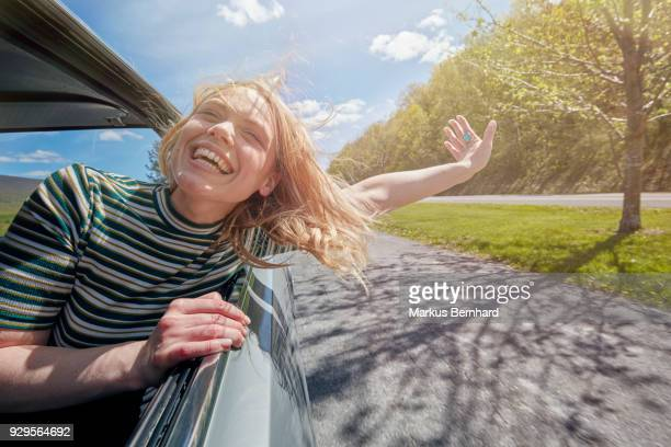 woman sticking head out of window while driving - ontsnappen stockfoto's en -beelden