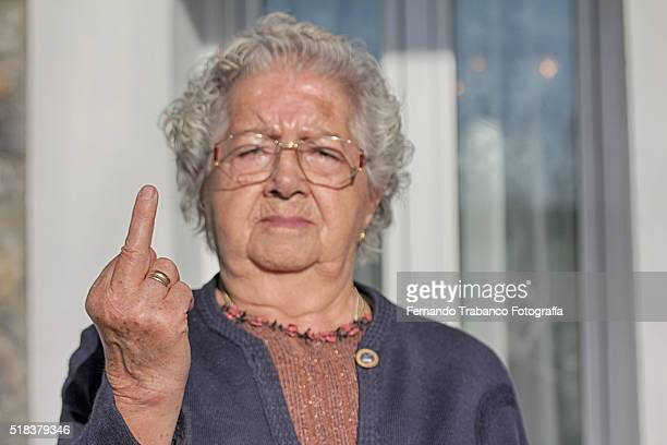 woman sticking up her middle finger - old lady middle finger stock pictures, royalty-free photos & images