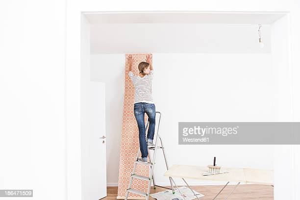 woman sticking wallpaper on wall - step ladder stock photos and pictures