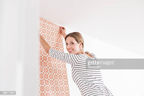 Woman sticking wallpaper on wall, smiling