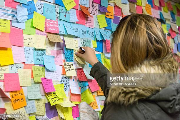 A woman sticks a PostIt note to participate in the art piece 'Subway Therapy' at the Union Square subway station in New York on November 17 2016...