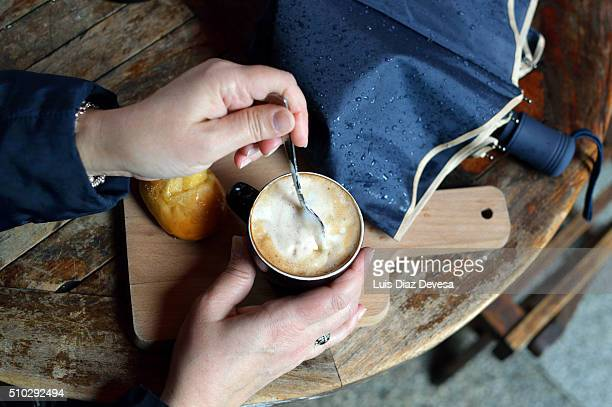 Woman stirring a cup of coffee with milk