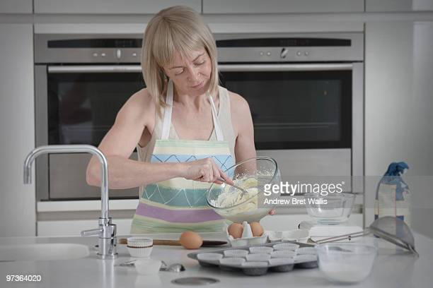 woman stirring cake mixture to make buns