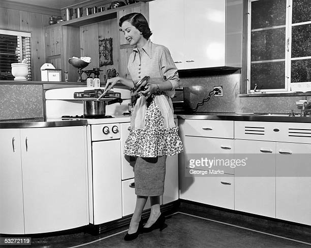 Woman stirring pot at stove
