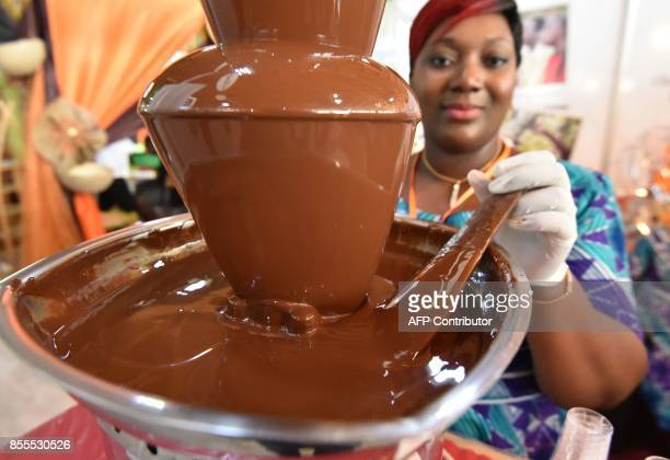A woman stirs a chocolate fountain at a cocoa and chocolate stand on September 29 2017 in Abidjan during the national cocoa and chocolate days Ivory...