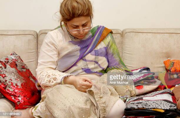a woman stitching clothes with a needle and thread while sitting on sofa in a living room. - fashion collection stock pictures, royalty-free photos & images