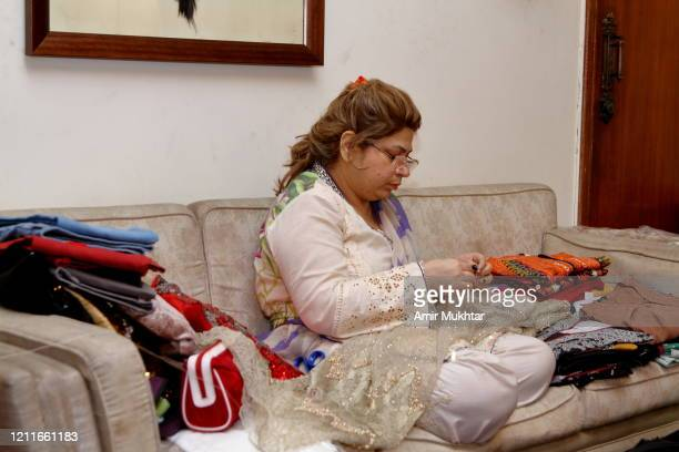 a woman stitching clothes with a needle and thread while sitting on sofa in living room. - fashion collection stock pictures, royalty-free photos & images
