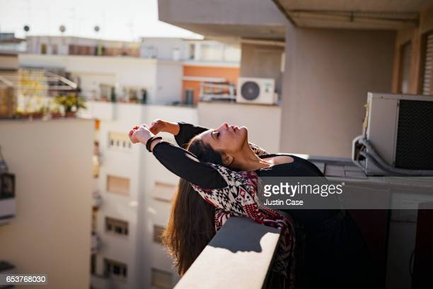 woman stitching out into the sunlight on her balcony