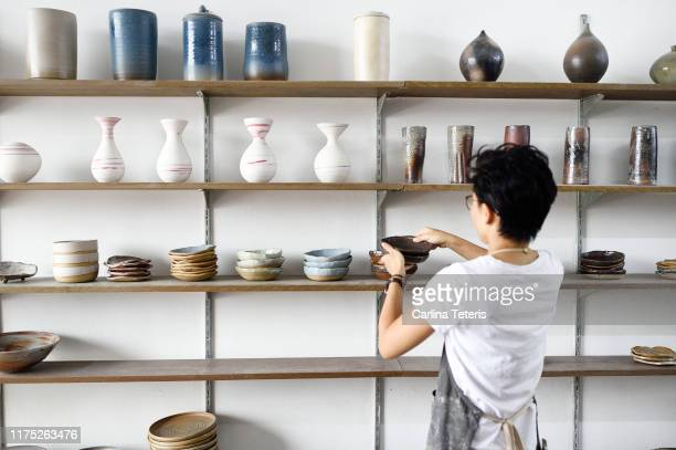 woman stocking shelves in a ceramics shop - craft product stock pictures, royalty-free photos & images