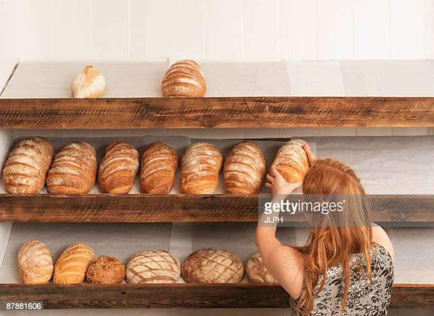 Woman stocking shelves in bakery