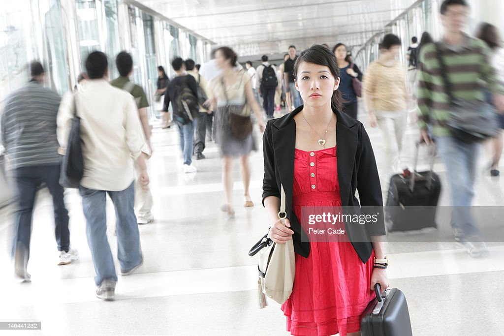 woman stood alone in busy walkway : Stock Photo