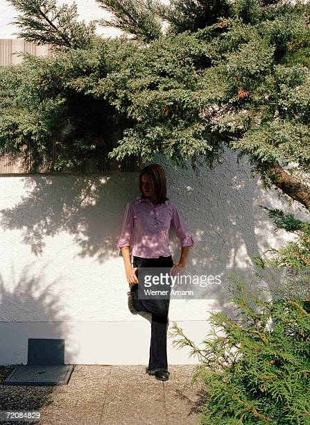 Woman stood in shade below tree