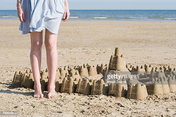 Woman stood next sandcastle
