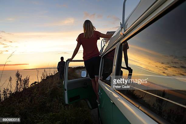 woman stood on camper looking at view, man ahead - camper van stock pictures, royalty-free photos & images
