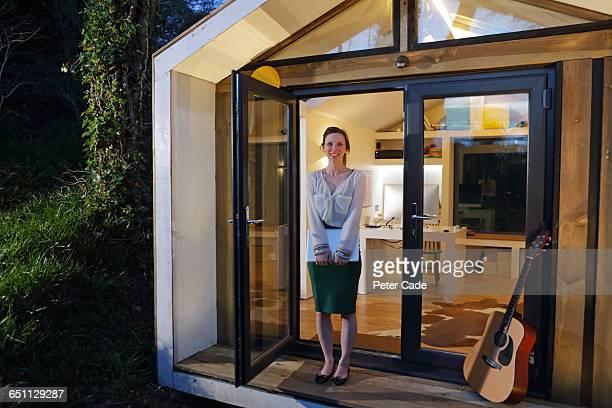 Woman stood outside home office in garden