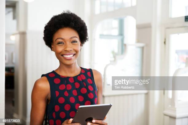 Woman stood, smiling with tablet