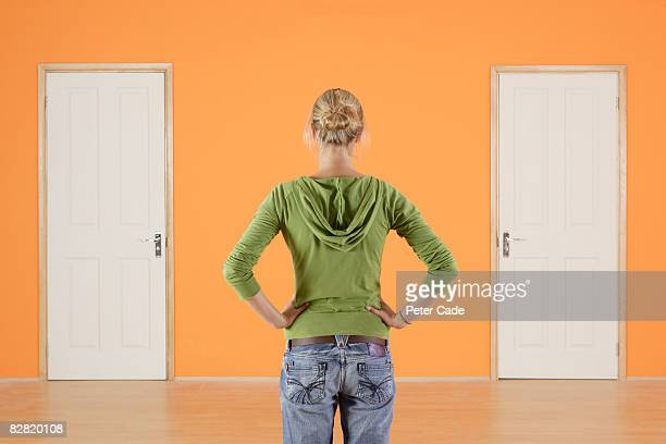woman stood with hands on hips looking at two door - decisions stock pictures, royalty-free photos & images