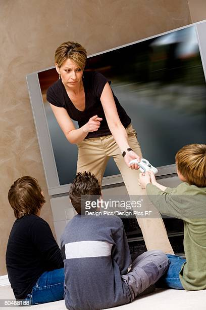 woman stopping boys from playing video game - stay at home mother stock-fotos und bilder