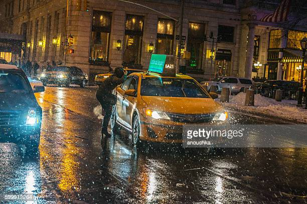 Woman stopping taxi during snow blizzard, NYC