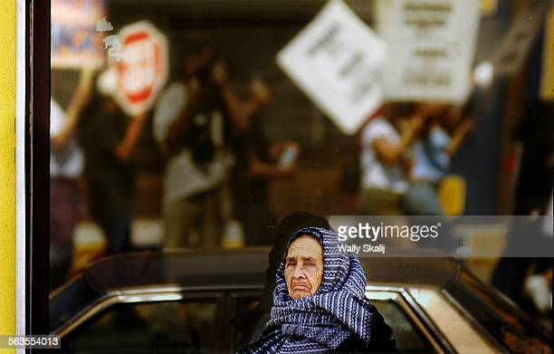 A woman stops along Whittier Blvd to watch anti–war protestors march in East Los Angeles Sunday