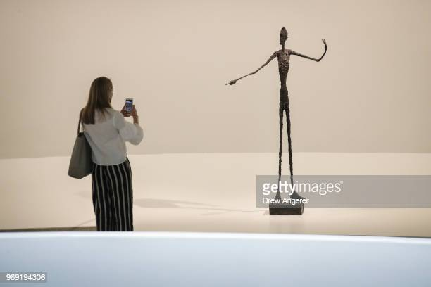 A woman stops and photographs 'Man Pointing' a 1947 bronze sculpture at a retrospective exhibition of work by Swiss sculptor and artist Alberto...