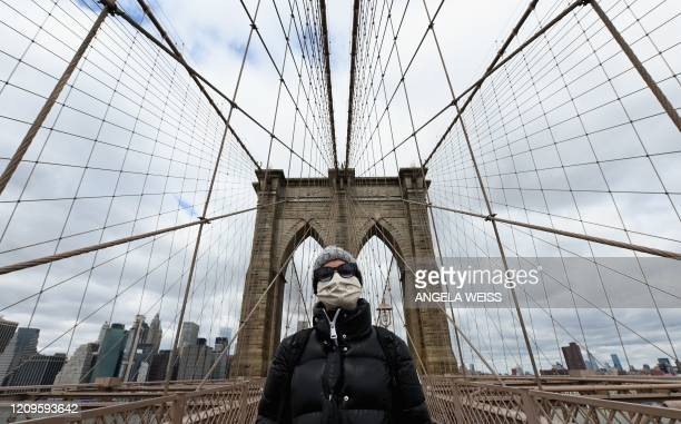 A woman stops for a picture on the Brooklyn Bridge on April 10 2020 in New York City Hundreds of millions of people around the world will spend the...