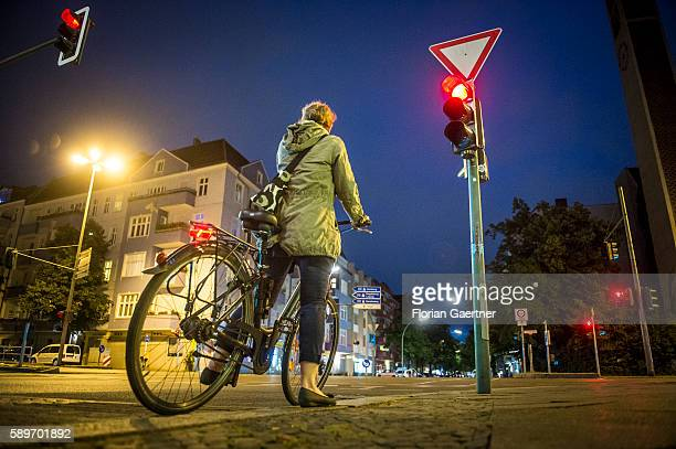 A woman stops riding her bike because of the red traffic light on August 09 2016 in Berlin Germany