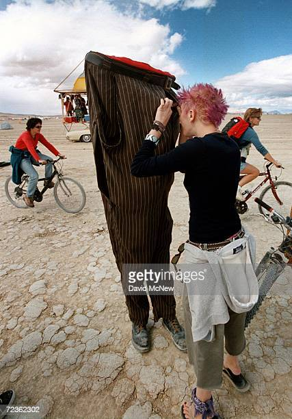 A woman stops to have a conversation with a walking pair of pants during the15th annual Burning Man festival September 2 2000 in the Black Rock...