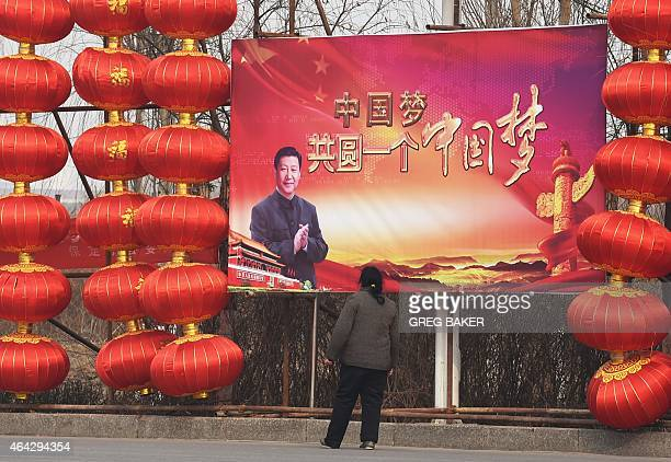 A woman stops to look at a billboard featuring a photo of Chinese President Xi Jinping beside lantern decorations for the Lunar New Year in Baoding...