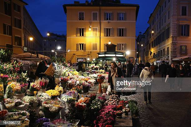 A woman stops to look at flowers in Campo de' Fiori on March 23 2013 in Rome Italy Today near Rome Pope Francis and Pope Emeritus Benedict met for a...