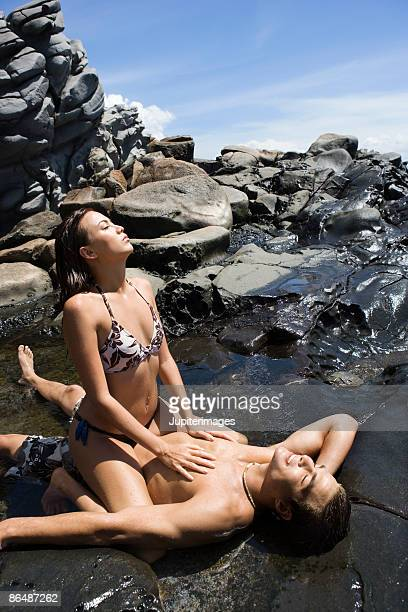 woman straddling man in tide pool - woman straddling man stock pictures, royalty-free photos & images