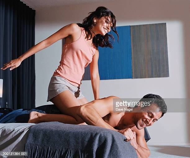 Woman straddling man on bed