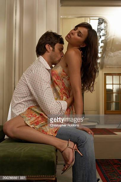 woman straddling man sitting on foyer bench, man kissing woman's chest - chest stock photos and pictures