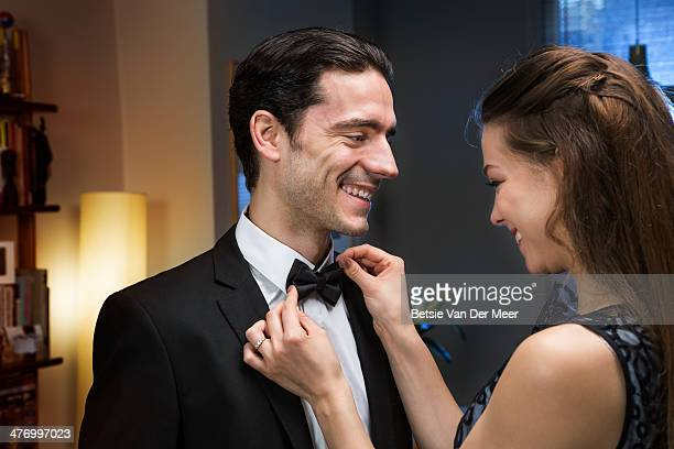 Woman straightens bow tie of man.