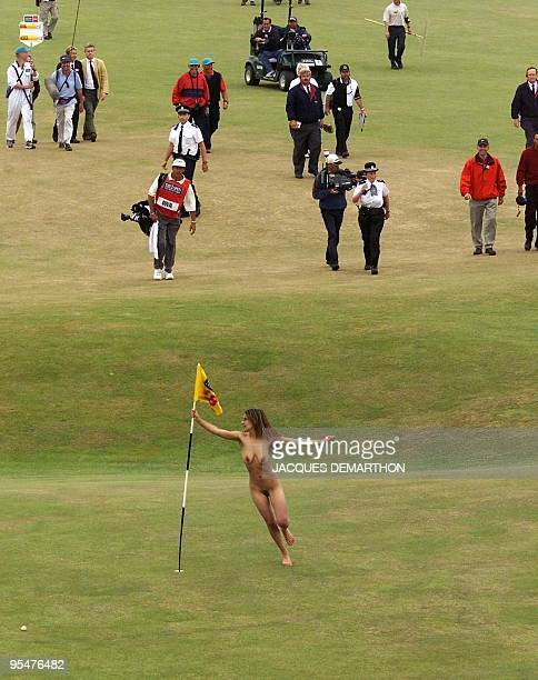 A woman streaker invades the 18th green at the arrival of the players at SaintAndrews 23 July 2000 during the last round of the 2000 British Golf...