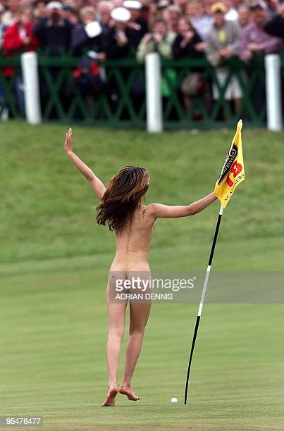 A woman streaker invades the 18th green to run around the flag just before the arrival of Tiger Woods onto the green on the Old Course at St Andrews...