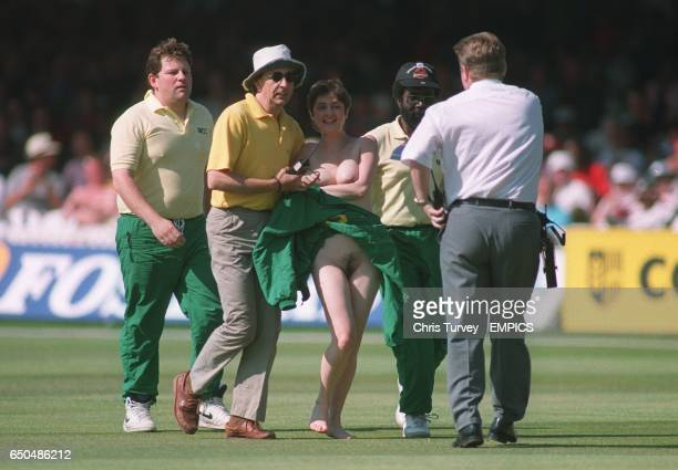A Woman streaker is escorted off the pitch
