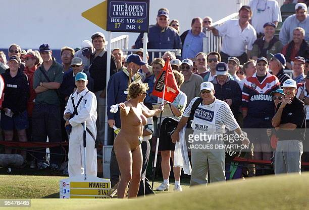 A woman streaker plays with flag on the 16th green after she invaded the Old Course at St Andrews during the second round of the British Open...