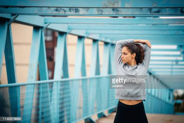 woman streching outdoors - warm up exercise stock pictures, royalty-free photos & images