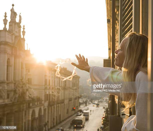 woman strecthes arms out apartment window, sunrise - turin stockfoto's en -beelden