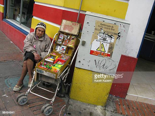 A woman street vendor sits in a corner in old part of the city Bogota formerly called Santa Fe de Bogota is the capital city of Colombia as well as...