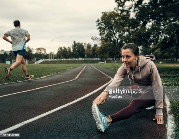 woman stretched on stadium track - vladgans or gansovsky stock pictures, royalty-free photos & images