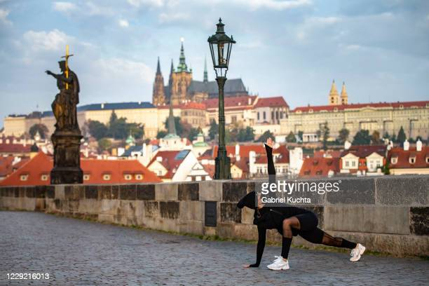 A woman stretches after a morning run at the medieval Charles Bridge on October 22 2020 in Prague Czech Republic The Czech Republic is under partial...