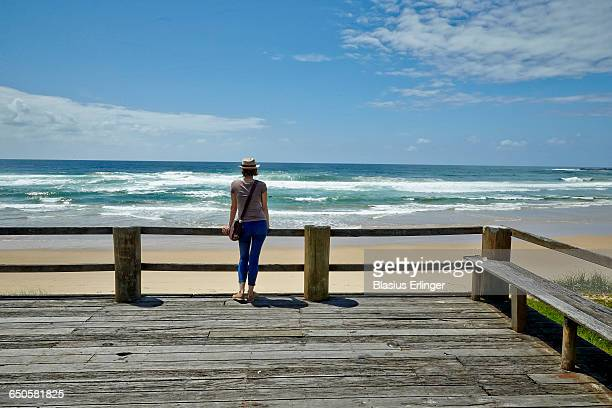 Woman stretches and gazes at the ocean