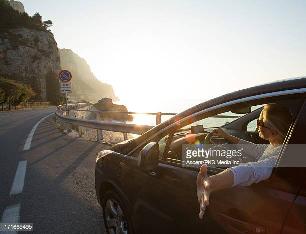 Woman stretches arm out of window, coastal road