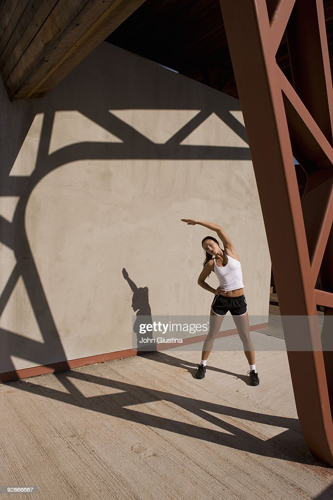 Woman stretches before working out. : Stock Photo