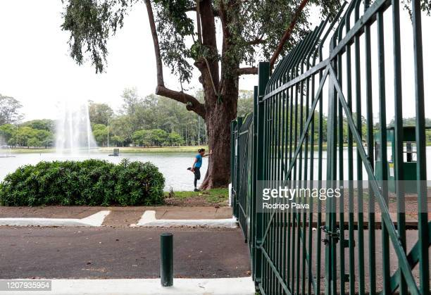 A woman stretches outside the gates of Ibirapuera Park during a lockdown aimed at stopping the spread of the coronavirus pandemic on March 21 in Sao...