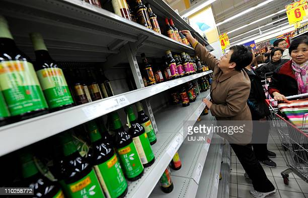 A woman stretches to get a bottle of soy sause on the shelf after salt sold out early at a supermarket in Beijing on March 17 2011 Chinese retailers...